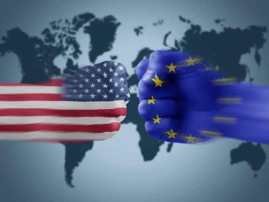 Zwei Fäuste in den Farben der Flaggen der USA und der EU prallen vor einer Weltkarte aufeinander